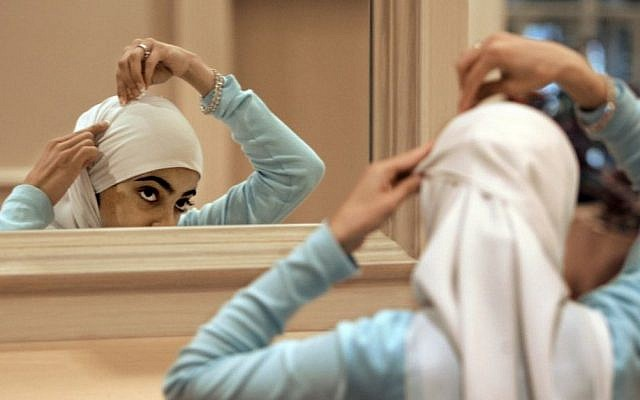 Illustrative photo of a Muslim woman adjusting her hijab. (AP/M. Spencer Green, File)
