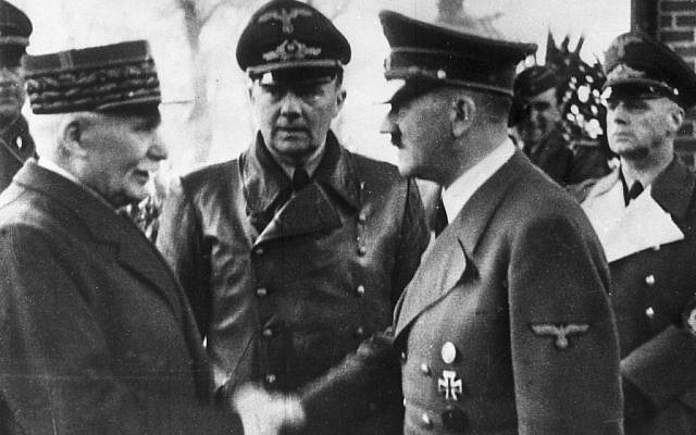 FILE - This Oct. 24, 1940 file photo shows German Chancellor Adolf Hitler, right, shaking hands with Head of State of Vichy France Marshall Philippe Petain, in occupied France. Behind center is Paul Schmidt, an interpreter, and right is German Minister of Foreign Affairs Joachim Von Ribbentrop. (AP Photo, File)