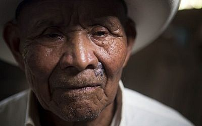 In this Dec. 11, 2015 photo, Fernando Osorio, a survivor of the Rio Negro massacre, poses for photos after giving his testimony to the Guatemalan Forensic Anthropology Foundation FAFG in Rabinal, Guatemala.  (AP Photo/Moises Castillo)