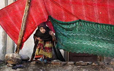 In this Nov. 29, 2015 photo, an internally displaced girl peeks from a tent after her family left their village in Rodat district of Jalalabad, Afghanistan. Nangarhar's chief refugee official says that at least 25,200 families, or more than 170,000 people, have been displaced across the province, either by Islamic State or perceived threats from the group. (AP Photo/Rahmat Gul)