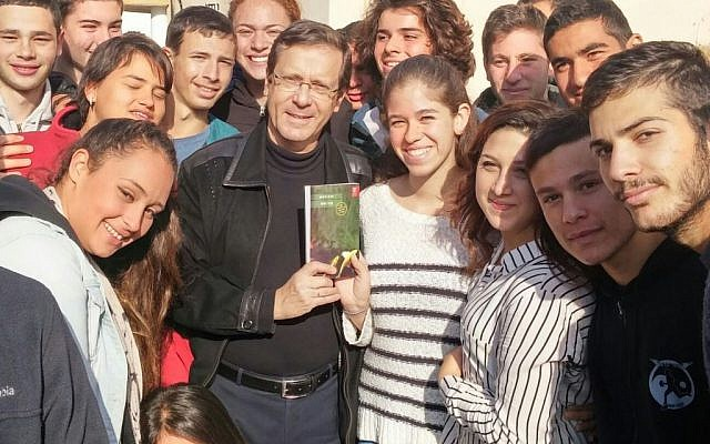 "Opposition leader Issac Herzog posing with a copy of Dorit Rabinyan's ""Gader Haya"" surrounded by students at the pre-army academy in Sderot, December 31, 2015. (Photo by Zionist Union)"