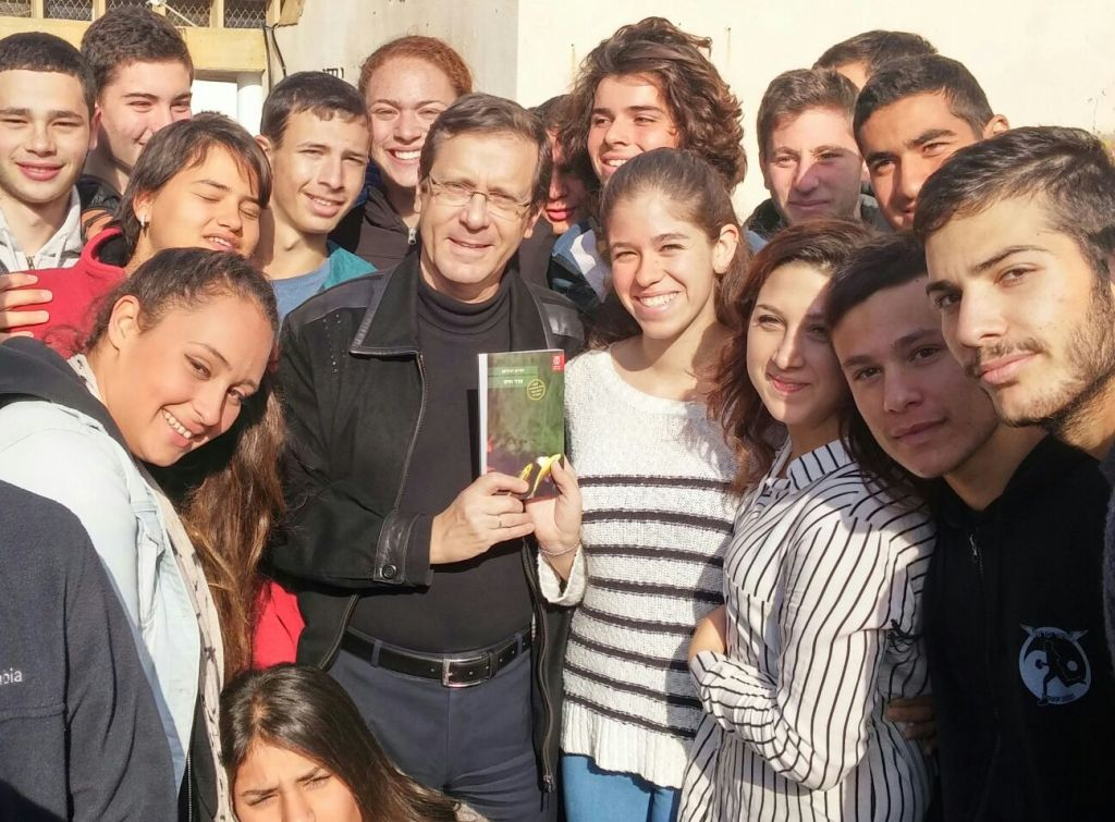 Opposition leader Issac Herzog posing with a copy of Dorit Rabinyan's 'All The Rivers,' originally called 'Borderlife,' surrounded by students at the pre-army academy in Sderot, December 31, 2015. (Photo by Zionist Union)
