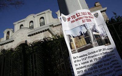 A poster asking for information about a string of arsons is displayed in the Forest Hills section of Queens in New York, Monday, Dec. 7, 2015. Over the past six weeks, an arsonist has torched six buildings in the same tight-knit section of eastern Queens, police say. Police aren't sure whether the victims are being targeted for their religion, their architectural taste, or for no reason at all. (AP Photo/Seth Wenig)