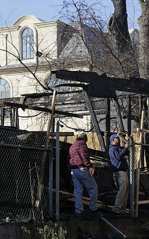 A large single family home rises above men working in the remains of a construction site that was destroyed by arson in the Forest Hills section of Queens in New York, Monday, Dec. 7, 2015. Over the past six weeks, an arsonist has torched six buildings in the same tight-knit section of eastern Queens, police say. Police aren't sure whether the victims are being targeted for their religion, their architectural taste, or for no reason at all. (AP Photo/Seth Wenig)