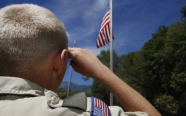 A Boy Scout salutes the American flag at camp Maple Dell outside Payson, Utah, on July 31, 2015. (George Frey/Getty Images via JTA)