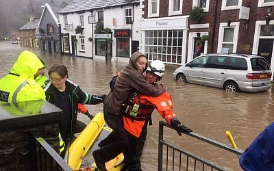 A man is helped by a rescue team in Whalley, Lancashire, England, Saturday Dec. 26, 2015. (Kim Pilling/PA via AP)