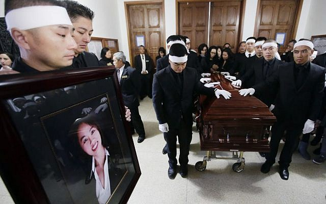 San Trinh, left, holds a portrait of his fiance Tin Nguyen at her funeral on Saturday, Dec. 12, 2015 in Santa Ana, Calif. Nguyen died in the mass shootings in San Bernardino, Calif., Wednesday, Dec. 2. (AP Photo/Chris Carlson)