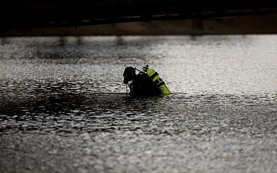 A member of the FBI dive team searches Seccombe Lake Friday, Dec. 11, 2015, in San Bernardino, Calif., for evidence in connection with last week's fatal shooting at Inland Regional Center. The FBI says divers are searching the lake because leads indicate the shooters who killed 14 people at a holiday party had been in the area. (AP Photo/Jae C. Hong)