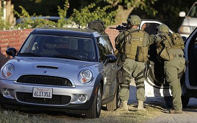 Law enforcement search for a suspect in a mass shooting that occurred at a Southern California social services center on Wednesday, Dec. 2, 2015, in San Bernardino, California. (AP/Chris Carlson)
