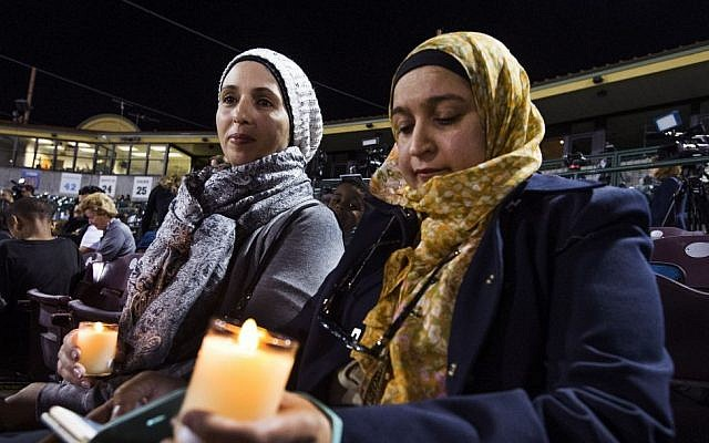 Rania Elbanna, 40, left, and Dr. Shaheen Zakaria, friends from Loma Linda, California, hold candles at a vigil at San Manuel Stadium Thursday, Dec. 3, 2015, in remembrance of the 14 people lost Wednesday in the San Bernardino mass shooting. (Tom Tingle/The Arizona Republic via AP)