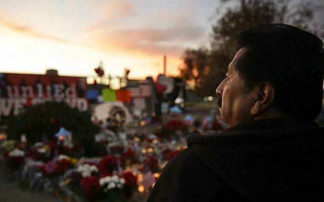 John Ramos, 58, of Riverside, California, pays his respects at a makeshift memorial site honoring Wednesday's shooting victims Monday, Dec. 7, 2015 in San Bernardino, California. (AP Photo/Jae C. Hong)