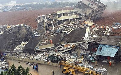 Rescuers search for survivors among collapsed buildings after a landslide in Shenzhen, in south China's Guangdong province, Sunday Dec. 20, 2015. (Chinatopix via AP)