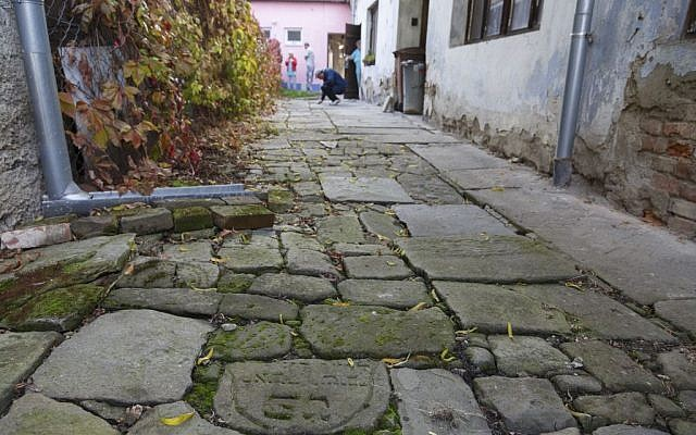 In this picture taken on Monday Oct. 26, 2015, Tomas Jelinek looks at pavement made of tombstones in efforts to restore a former Jewish cemetery in Prostejov, Czech Republic. (AP Photo/Petr Josek)