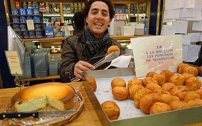 Dmitri Kahn serving ponchkes (donuts) at his mother's bakery Rue des Rosiers, in the heavily Jewish Marais neighborhood. (Greg Scrugg/The Times of Israel)