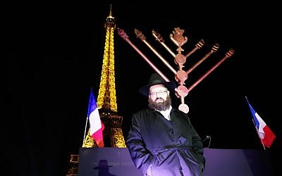 Rabbi Mendel Azimov, president of Chabad of Paris, lit a Hanukkah menorah in front of the Eiffel Tower on December 6, 2015. (Greg Scruggs/The Times of Israel)