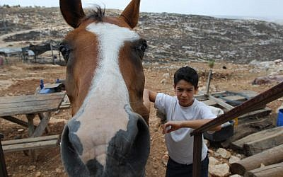 A child and a horse at a West Bank outpost in 2009. Illustrative photo. (Gili Yaari / Flash 90)