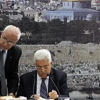 PA President Mahmoud Abbas (R) and chief peace negotiator Saeb Erekat sign an application to join UN agencies, in the West Bank city of Ramallah, on Tuesday, April 1, 2014. (Issam Rimawi/Flash90)