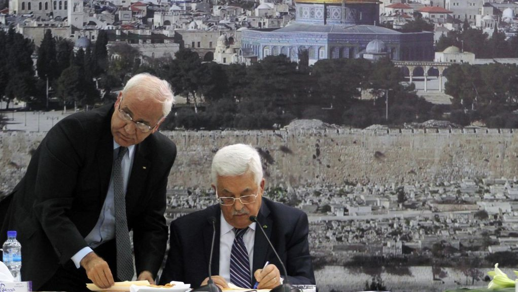 PA President Mahmoud Abbas (R) and chief peace negotiator Saeb Erekat sign an application to join UN agencies, in the West Bank city of Ramallah on Tuesday, April 1, 2014 (Issam Rimawi/Flash90)