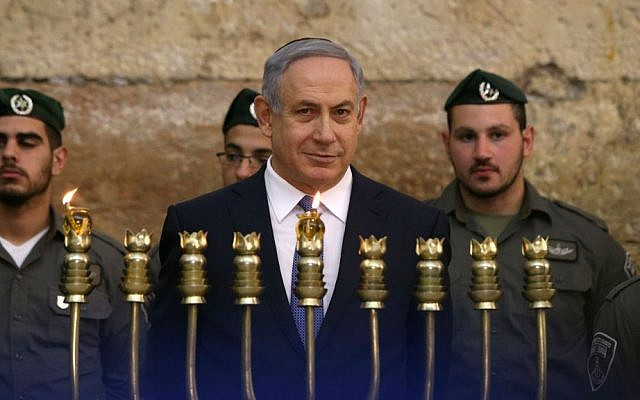 Prime Minister Benjamin Netanyahu lights the first candle of Hanukkah with Border Police officers at the Western Wall in Jerusalem, December 6, 2015. (Amit Shabi/Pool/Flash90)