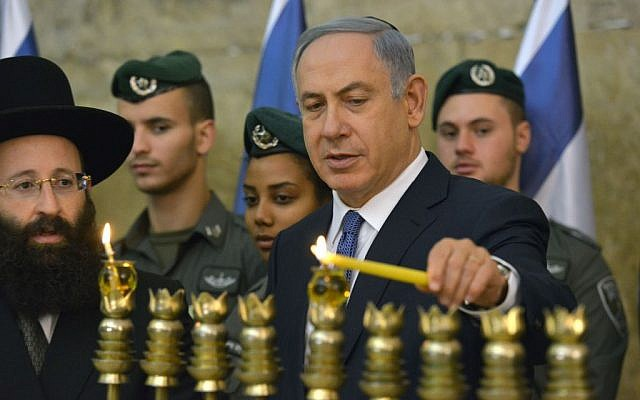 Prime Minister Benjamin Netanyahu lights the menorah on the first night of the Jewish holiday of Hanukkah at the Western Wall in Jerusalem Old City on December 6, 2015. (Kobi Gideon/GPO)