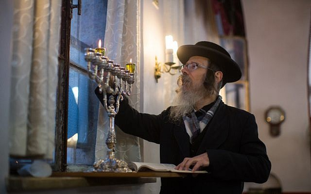 An ultra-Orthodox Jewish man lights candles for the Jewish holiday of Hanukkah in Jerusalem's Mea Shearim neighborhood on December 6, 2015. (Yonatan Sindel/Flash90)