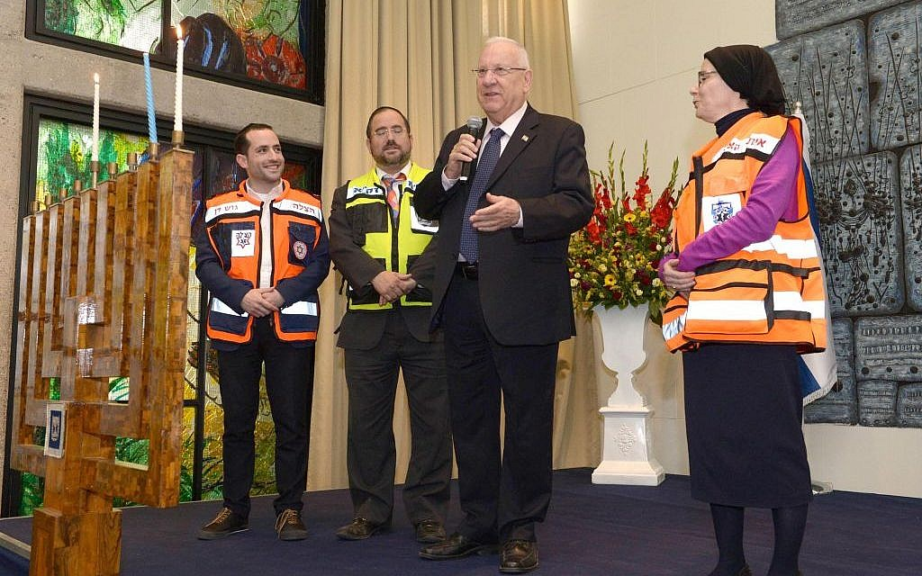 President Reuven Rivlin lighting the second candle on Hanukkah together with 100 representatives of rescue organizations, on December 7, 2015. (Mark Neyman/GPO)