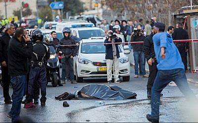 The body of a Palestinian terrorist lies in the road after he was shot dead by Israeli security personnel during a terror attack at the entrance to Jerusalem on December 14, 2015, that injured 14 people, including a baby. (Photo by Yonatan Sindel/Flash90)
