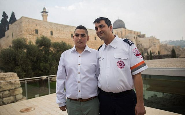 13-year-old Naor Shalev Ben-Ezra poses for a picture with the paramedic who saved his life as he celebrates his bar-mitzvah with family and friends at the Western Wall in Jerusalem's Old City on December 17, 2015. (Yonatan Sindel/Flash90)