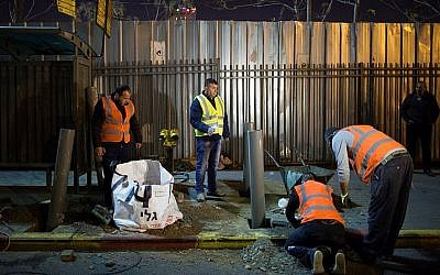 Israeli and Palestinian laborers place barriers at a bus stop in Jerusalem on December 20, 2015, after a terror attack there last week. (Yonatan Sindel/Flash90)