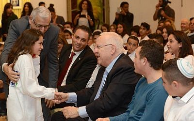 President Reuven Rivlin, center, greets a young girl celebrating her bat mitzvah at the President's Residence, Jerusalem, December 21, 2015. (Mark Neiman/GPO)