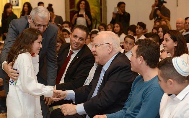 President Reuven Rivlin, center, greets a young girl celebrating her bat mitzvah at the President's Residence, Jerusalem, December 21, 2015. (Mark Neiman/GPO)