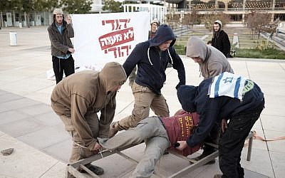 Right-wing Jewish activists protest against alleged torture by the Shin Bet security service by reenacting the supposed techniques in Habima square in Tel Aviv on December 23, 2015.(Tomer Neuberg/Flash90)