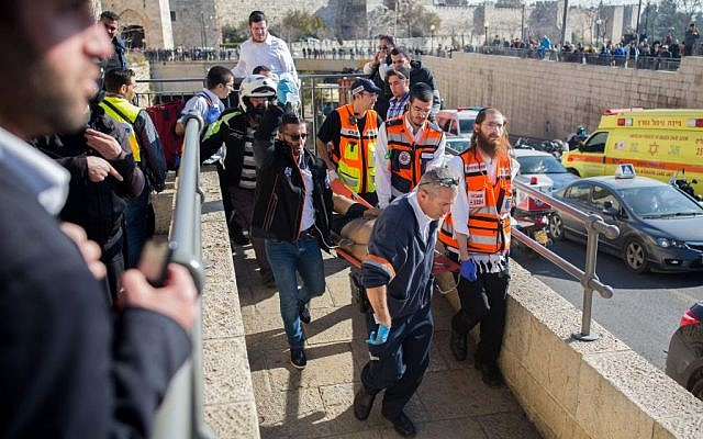 Rescue and medical personnel carrying a wounded man at the scene of a stabbing attack at the Old City's Jaffa Gate in Jerusalem on December 23, 2015. (Yonatan Sindel/Flash90)