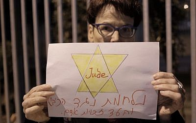 """A Peace Now activists holding a sign reading """"fighting against the occupation and for human rights"""" at a protest against the NGO bill in Tel Aviv on December 26, 2015. (Tomer Neuberg/FLASH90)"""