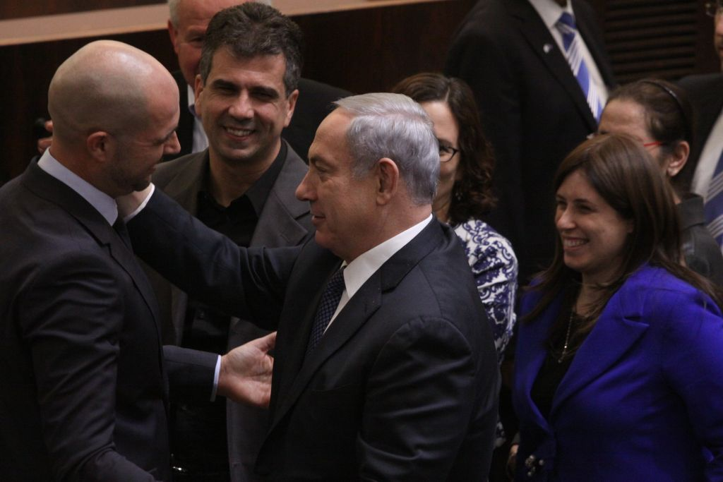 New Likud MK Amir Ohana is congratulated by Prime Minister Benjamin Netanyahu after his swearing-in, on December 28, 2015. (Isaac Harari/FLASH90)