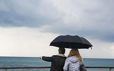 A couple holding an umbrella on a rainy day look out over the sea, at the Tel Aviv port. (December 18, 2015. (Esther Rubyan/FLASH90)