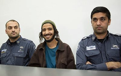 Yakir Ashbel (center), the groom from what came to be known as the 'hate wedding,' is brought to the Jerusalem Magistrate's Court on December 31, 2015 after being arrested on suspicion of racist incitement at his wedding celebration. (Flash90)