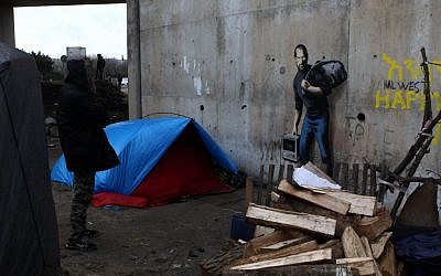 A painting by English graffiti artist Banksy is seen at the entrance of the Calais refugee camp in France, Saturday, Dec. 12, 2015. (AP Photo/Michel Spingler)