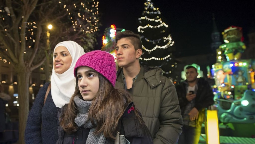Syrian refugees Reem Habashieh, Raghad Habashieh, Yaman Habashieh and Mohammed Habashieh, from left to right, visit the Christmas market in Zwickau, eastern Germany on Tuesday, Dec. 8, 2015. (AP Photo/Jens Meyer)