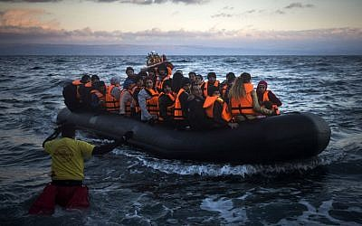 Refugees and migrants arrive on a dinghy from the Turkish coast to the Greek island of Lesbos, Friday, Dec. 18, 2015. (AP Photo/Santi Palacios)