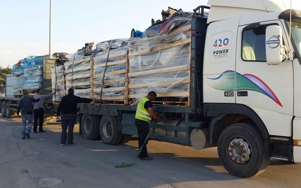 A Defense Ministry employee discovers bulletproof plating in a shipment of car parts on its way to the Gaza Strip through the Kerem Shalom Crossing on December 29, 2015. (Defense Ministry)