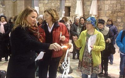 Member of Knesset Ksenia Svetlova lights a Hanukkah menorah at the Western Wall with Women of the Wall founding director Anat Hoffman (center), December 6, 2015. (Victoria Polak)