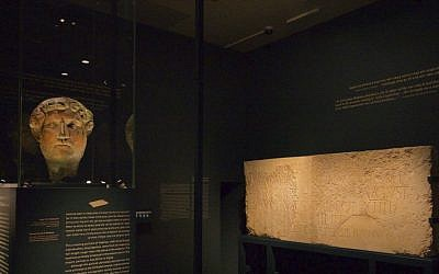 A bronze head of Roman Emperor Hadrian from the Louvre with a monumental inscription at an Israel Museum exhibit opening December 22, 2015. (Moti Tufeld)