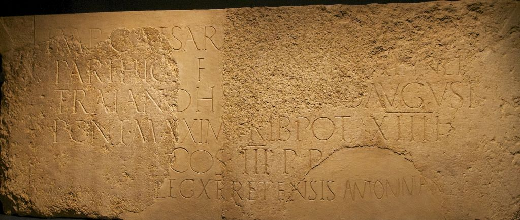 An inscription to Emperor Hadrian, whose two halves were found in Jerusalem over a century apart, rejoined at the Israel Museum. (Moti Tufeld)