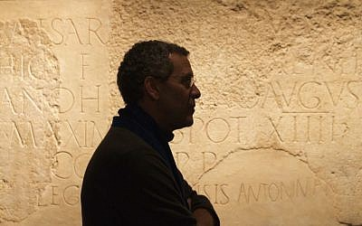 Curator David Mevorach and a monumental inscription dedicated to Roman Emperor Hadrian at an Israel Museum exhibit opening December 22, 2015. (Moti Tufeld)