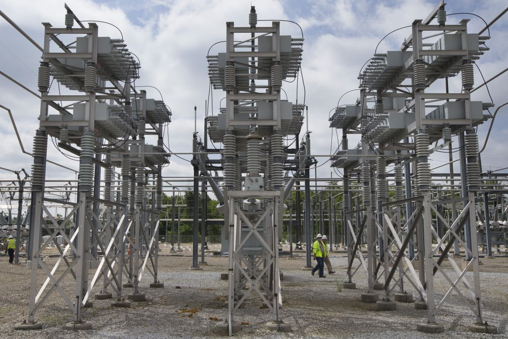 Contractors walk past a capacitor bank at an AEP electrical transmission substation in Westerville, Ohio on May 20, 2015. (AP Photo/John Minchillo)