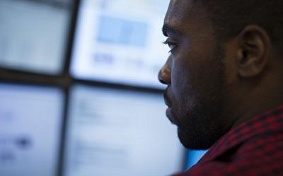 Eric Dinkins, cyber security analyst associate, works at a computer station in the Cyber Security Operations Center at AEP headquarters in Columbus, Ohio on May 20, 2015. (AP Photo/John Minchillo)