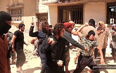 In this picture posted on a social media account affiliated with the Islamic State group on June 14, 2015, IS militants stone a man accused of violating the extremists' ban on homosexuality after they threw him from a roof in the city of Homs, Syria. (Photo via AP)