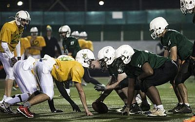 High school football team Kfar Saba Hawks, in green shirts, play against Mazkeret Batya Gorillas in Kfar Saba, December 10, 2015. (AP/Dan Balilty)