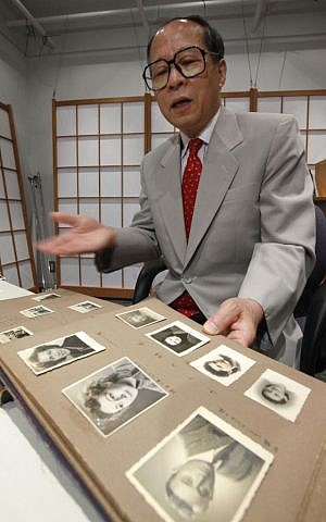 FILE - In this July 26, 2010 file photo, Akira Kitade displays a photo album that belonged to a former colleague of his at the Japan Tourist Bureau, Tatsuo Osako, during an interview in Tokyo. (Shizuo Kambayashi/AP)